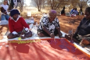 Warakurna community, WA - Tjapartji Bates, Christine West and Dorcas Bennett working on the Seven Sisters Tjukurrpa collaborative painting