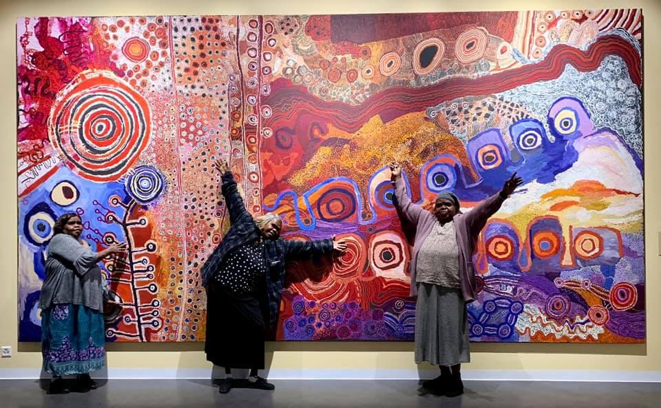 Artists Nyunmiti Burton, Tuppy Goodwin and Mrs Norris in front of collaborative painting 'Nganampa mantangka minyma tjutaku Tjukurpa ngaranyi alatjitu' 2018 at Fondation Opale - Photo Fondation Opale